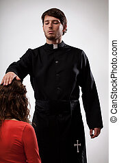 Priest is blessing a believer - Priest in black cassock...