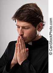 Vicar praying earnestly - Vicar praying to God with closed...