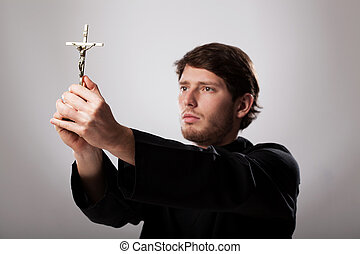Priest holding crucifix - Priest holding a golden crucifix...