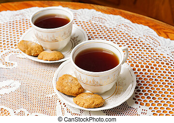 Two tea cups with gold - Two full tea cups with cookies,...