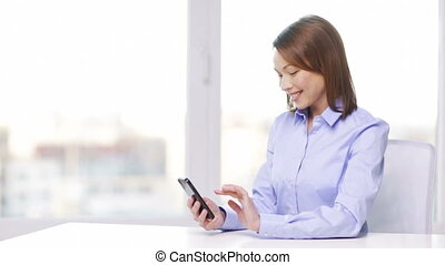 smiling businesswoman with smartphone in office