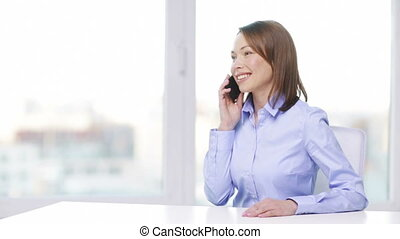 smiling businesswoman with smartphone in office - business,...