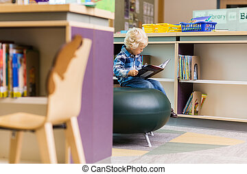 Boy Reading Book In Library - Boy reading book in library of...