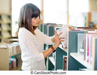 Student Selecting Books In Bookstore - Young university...