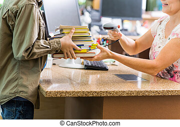 Schoolboy Holding Books At Library Counter - Midsection of...