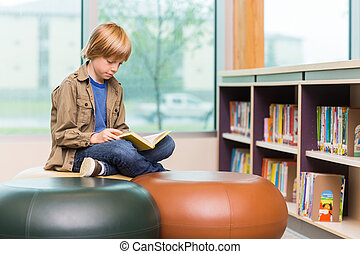 Boy Reading Book In Library - Young boy reading book in...