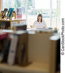 Student With Laptop Studying In Library - Portrait of female...