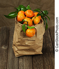 Fresh tangerines with leaves in recycle paper bag on wooden table. Closeup.