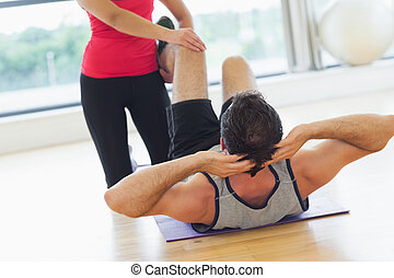 Female trainer assisting man with his exercises in gym - Mid...