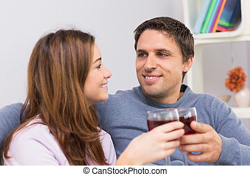 Smiling couple toasting wine glasses at home