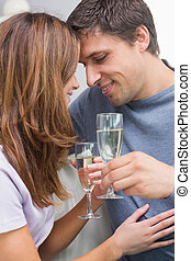 Close-up of a romantic couple with flutes at home