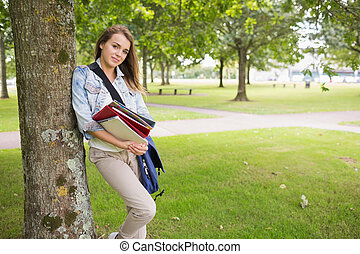Cheerful student leaning on tree holding her books on...