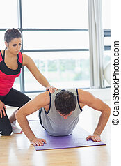 Female trainer assisting man with push ups in gym