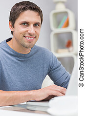 Smiling man using laptop in living room - Portrait of a...