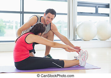 Trainer assisting woman with pilate exercises in fitness...