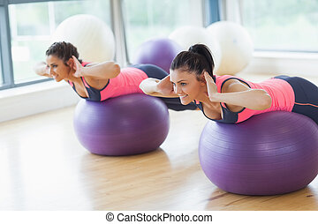 Two fit women exercising on fitness balls in gym - Two fit...