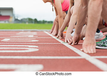 Side view of cropped people ready to race on track field -...