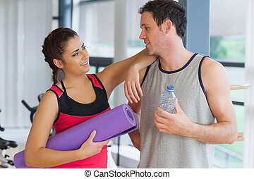 Fit couple with water bottle and exercise mat in exercise...