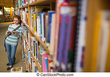 Focused student reading book leaning on shelf in library at...