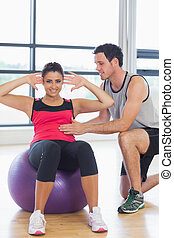 Trainer helping woman do abdominal - Male trainer helping...