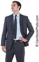 Serious businessman with hand on hip on white background