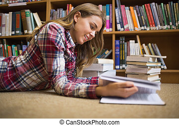 Smiling student lying on library floor reading in college