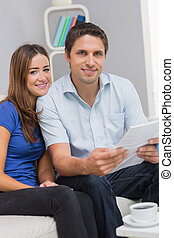 Smiling couple with bills in living room at home
