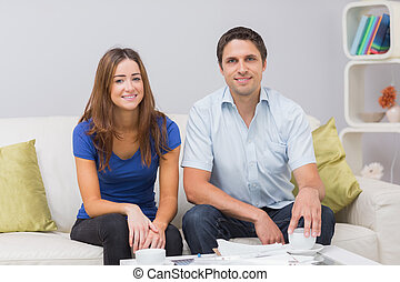Portrait of a smiling young couple with bills at home