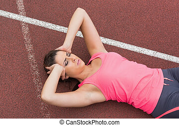 Sporty woman suffering from headache on the running track -...