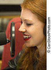 Pretty redhead student presenting a radio show in college
