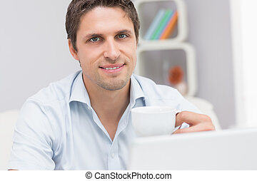 Close-up of man with teacup using laptop at home