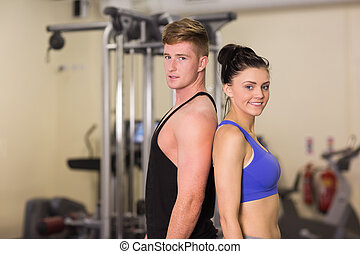 Sporty woman and man standing back to back in the gym - Side...