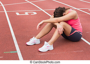 Tensed sporty woman sitting on the running track - Full...
