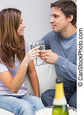 Romantic couple toasting flutes in the living room