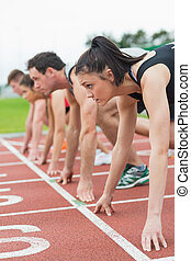 Young people ready to race on track field - Side view of...