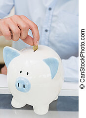 Close-up mid section of a man putting coin into piggy bank -...