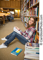 Cheerful student reading book on library floor