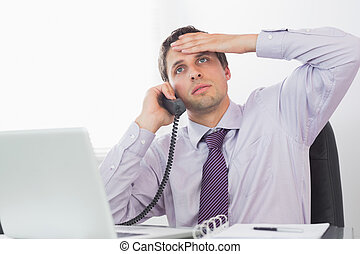 Worried businessman on call at desk - Worried businessman on...