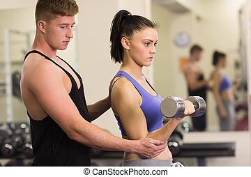 Male trainer helping woman with the dumbbells in gym