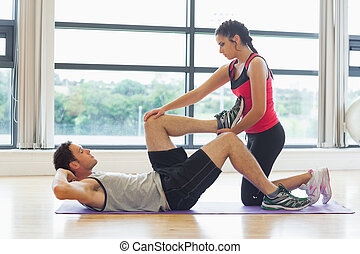Female trainer assisting man with his exercises in gym -...