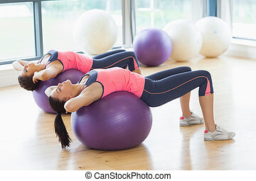 Two fit women stretching on fitness balls in gym - Two fit...