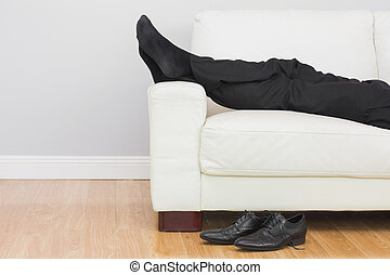 Low section of businessman resting on sofa in living room -...