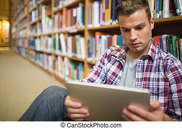 Serious young student sitting on library floor using tablet...