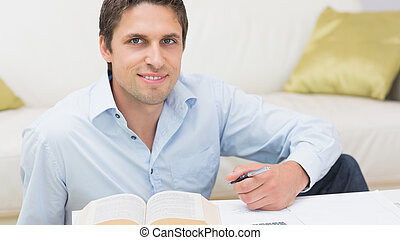 Portrait of a man with pen and book at home