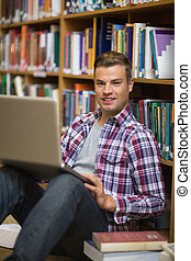 Happy young student sitting on library floor using laptop