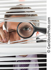 Businessman peeking through blinds with magnifying glass -...