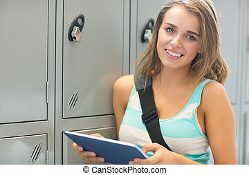 Cheerful student using her tablet beside lockers looking at...