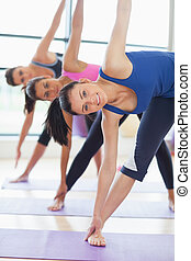 Class doing stretching pilate exercises in fitness studio -...