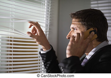 Businessman peeking through blinds while on call in office -...