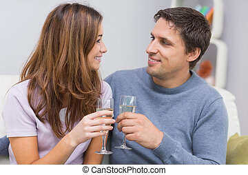 Romantic smiling young couple toasting flutes at home